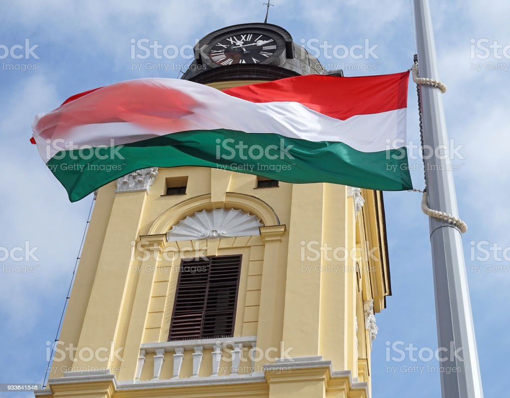 Hungarian flag on a pole next to a chuch tower stock photo
