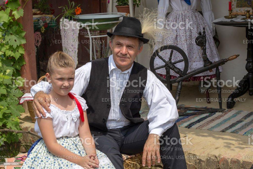 Grand-père hongrois et petite-fille de Banat, en costumes traditionnels - Photo