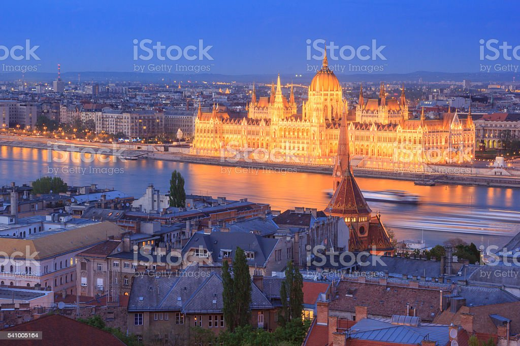 Hungarian Parliament Building By Danube River In City Against Sky stock photo