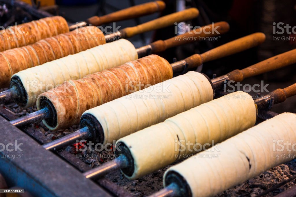 Hungarian sweet food Kürtőskalács being cooked outside at food market stock photo