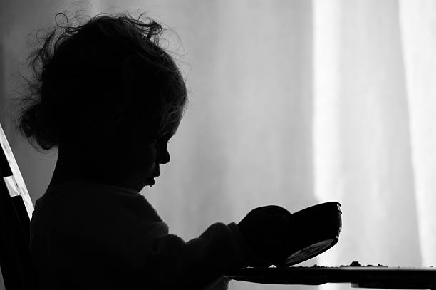 Hunger (XL) A two year old girl is sadly looking into her empty bowl wishing she had more to eat. hungry stock pictures, royalty-free photos & images