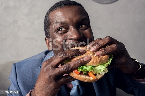 973213156 istock photo hungry african american businessman eating hamburger 973212774