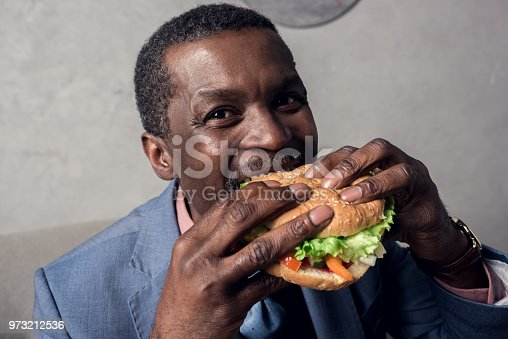 973213156 istock photo hungry african american man eating hamburger 973212536