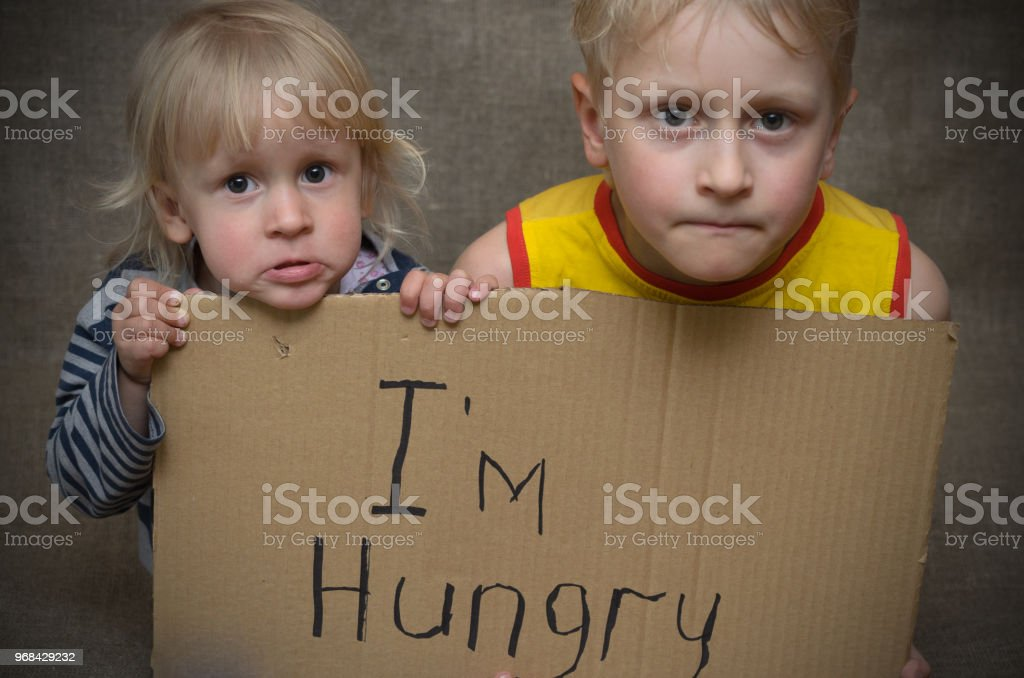 A hungry boy and a girl with a cardboard tablet with the inscription I'm hungry . royalty-free stock photo