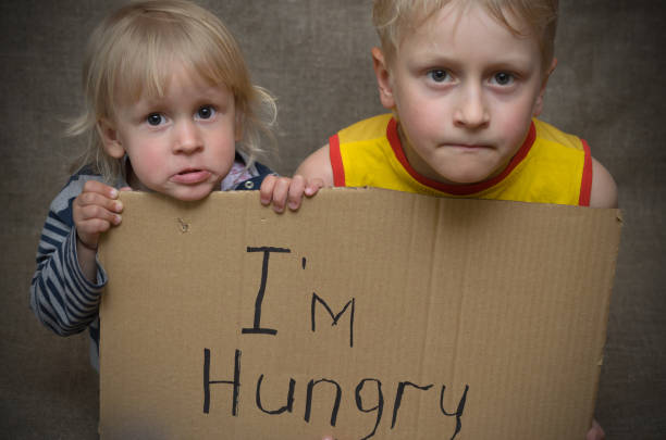 A hungry boy and a girl with a cardboard tablet with the inscription I'm hungry . A hungry boy and a girl with a cardboard tablet with the inscription I'm hungry . hungry stock pictures, royalty-free photos & images