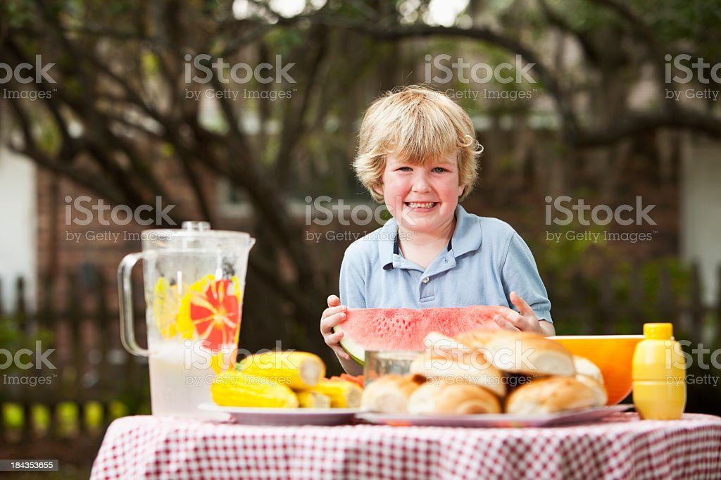 Hungry boy with watermelon stock photo