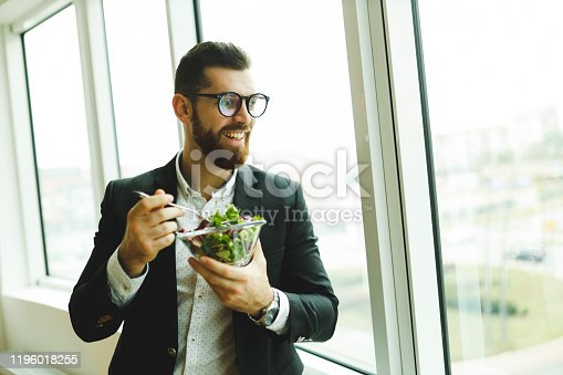 Hungry businessman eating salad and standing near office window