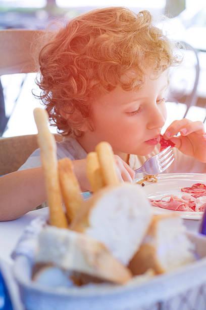 bambino affamato mangia utilizzando bivio e le mani - bresaola foto e immagini stock
