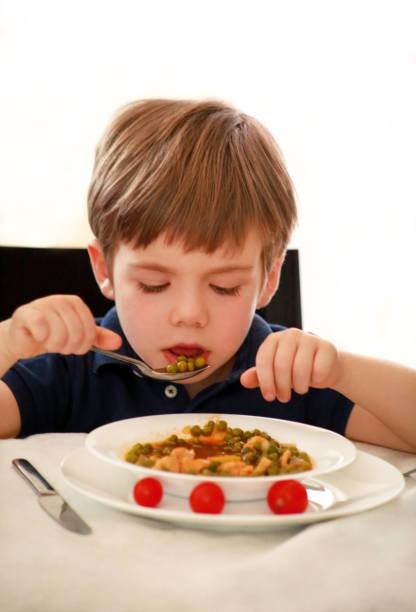 Criança com fome que senta-se na cadeira na tabela na cozinha e que come com a colher de ervilhas cozinhadas com tomate. Refeição dos miúdos e conceito saudável do alimento da dieta. Rapaz pequeno feliz e bonito que aprecia no bom almoço em casa. - foto de acervo