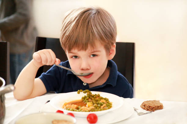 Hungry child sitting in chair at table in kitchen and eating with spoon of cooked peas with tomato. Kids meal and healthy diet food concept. Happy and cute little boy enjoying in good lunch at home. stock photo