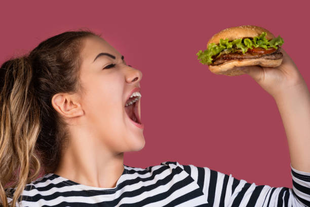 Hungry cool girl in striped t-shirt eating hamburger over pink background Crazy hungry cool girl in striped t-shirt eating hamburger in profile over colorful pink background female sandwich stock pictures, royalty-free photos & images