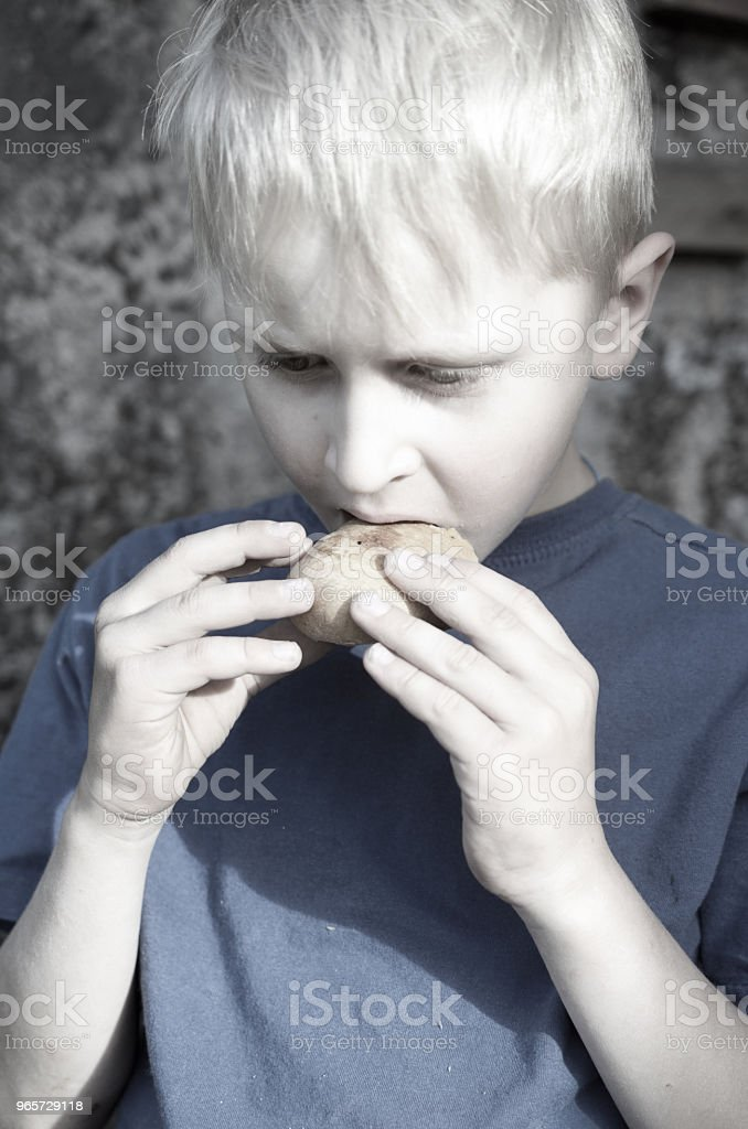 A hungry dirty boy greedily eats a crust of bread against the wall. Toning. - Royalty-free Allowance Stock Photo