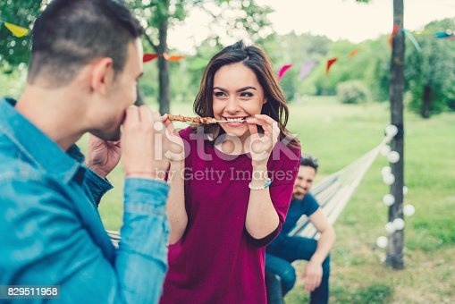696841580istockphoto Hungry friends enjoying food from the barbecue grill 829511958
