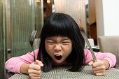 Little Asian girl waiting at table screaming for food