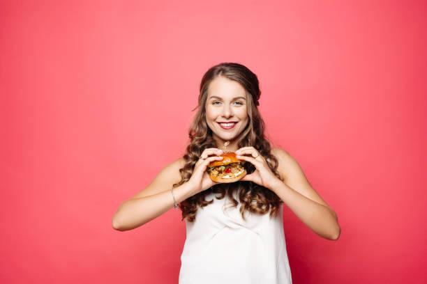 aç kız büyük hamburger yeme açtı ağız ile. - burger and chicken stok fotoğraflar ve resimler