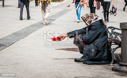 istock Hungry homeless beggar woman beg for money on the urban street in the city from people walking by, social documentary concept 940940592