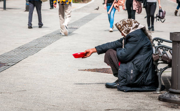 Hungry homeless beggar woman beg for money on the urban street in the city from people walking by, social documentary concept stock photo