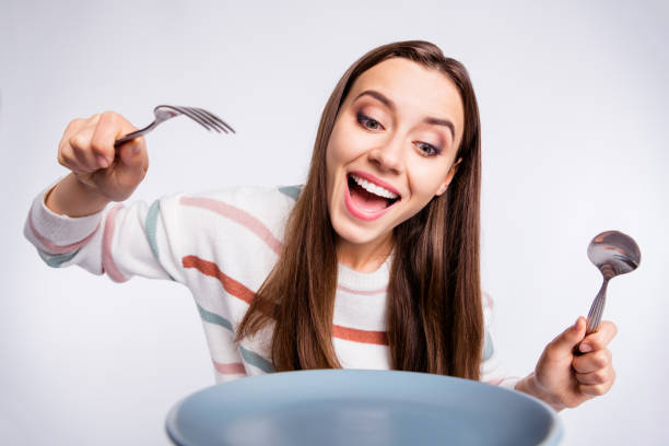饑餓的女士拿著叉子和勺子迫不及待地開始吃穿條紋拉過孤立的白色背景 - 即食口糧 個照片及圖片檔