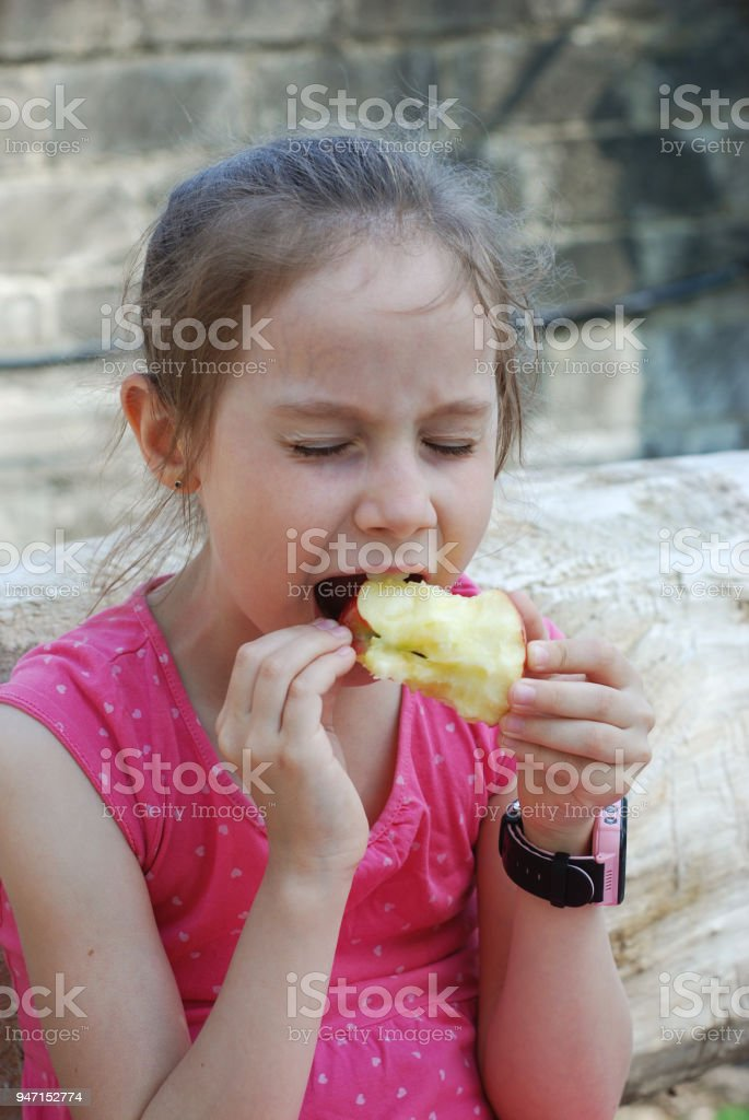 0100b83f665 Hungry Little Girl Portrait Eating Red Apple Outdoor Healthy Snack for Kids  Bite the Fruit Apple. girl in Pink Dress. - Stock image .