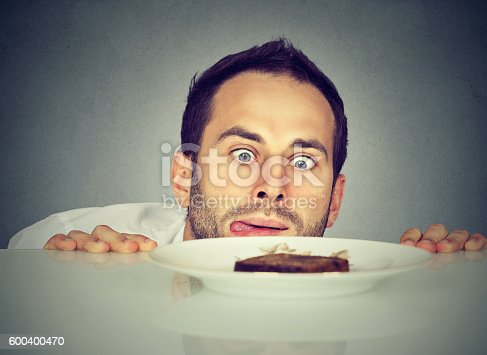 istock Hungry man craving sweet food 600400470