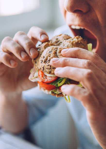 Hungry man eats a big sandwich stock photo