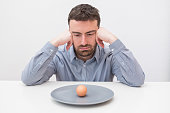 istock Hungry man feeling sad in front of a dish with an egg 959522990