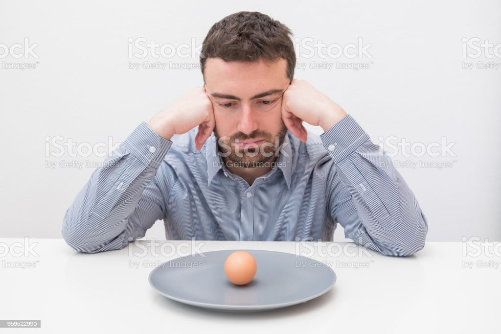 Hungry man feeling sad in front of a dish with an egg stock photo