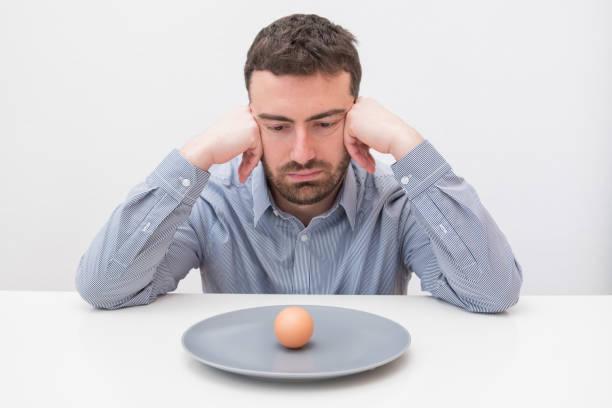 hungrigen mann traurig vor ein gericht mit einem ei - schmaler tisch stock-fotos und bilder
