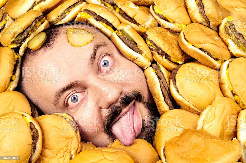 Hungry man half buried in a pile of hamburgers royalty-free stock photo