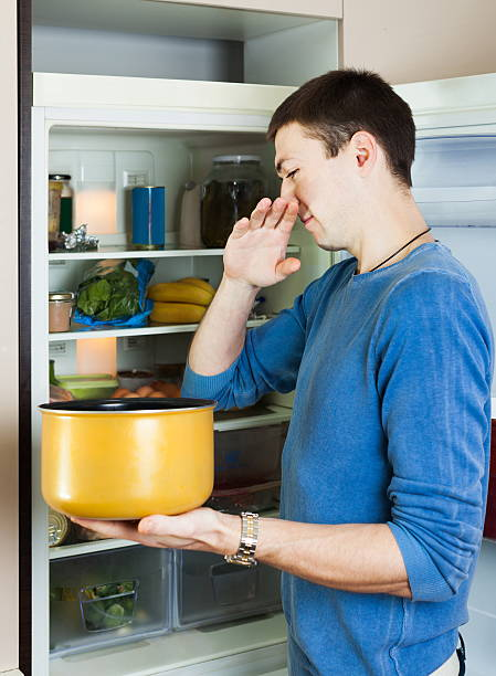 Hungry man holding foul food Hungry man holding foul food near refrigerator addle stock pictures, royalty-free photos & images