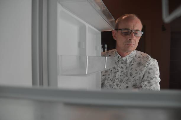 Hungry man looking for a late night meal in an empty fridge. Hungry man looking for a snack in the fridge at night, view from the fridge stock photo