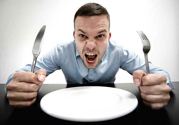 Hungry! man sitting on a table in front of an empty plate. knife and fork in his hands.he is screaming. he is hungry. hungry stock pictures, royalty-free photos & images
