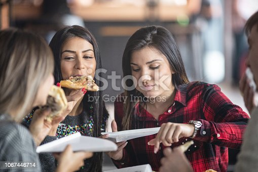 University student having fun while eating pizza in the college canteen