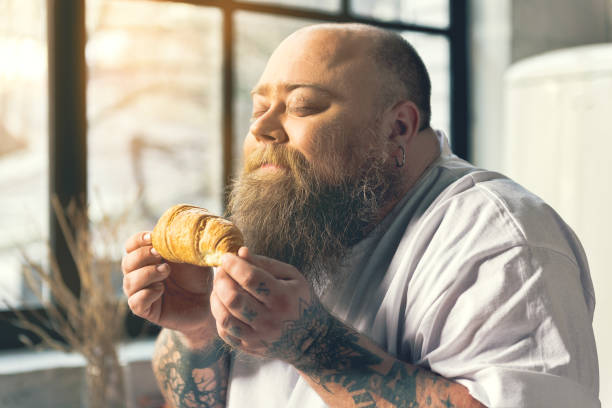 hungriger dicken mann duftendes croissant - geschlossene küchen stock-fotos und bilder