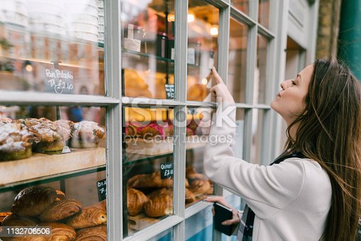 Young woman at the bakery choosing sweet food for breakfast