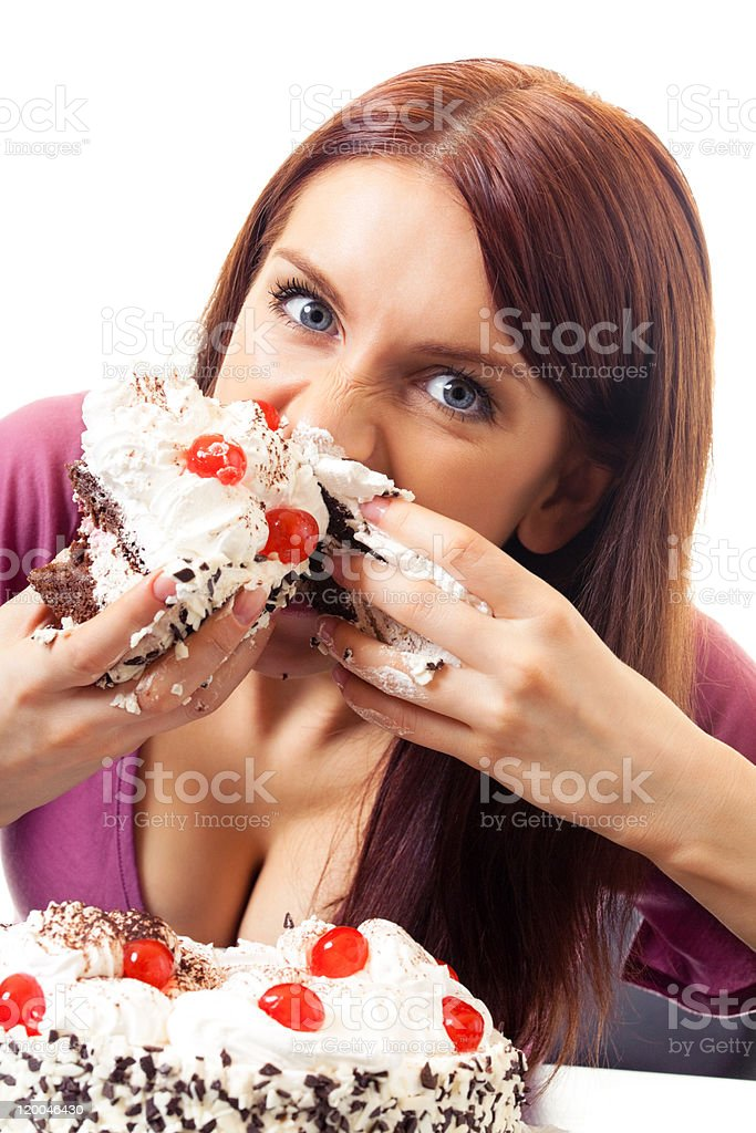 A hungry woman eating cake messily with her hands stock photo