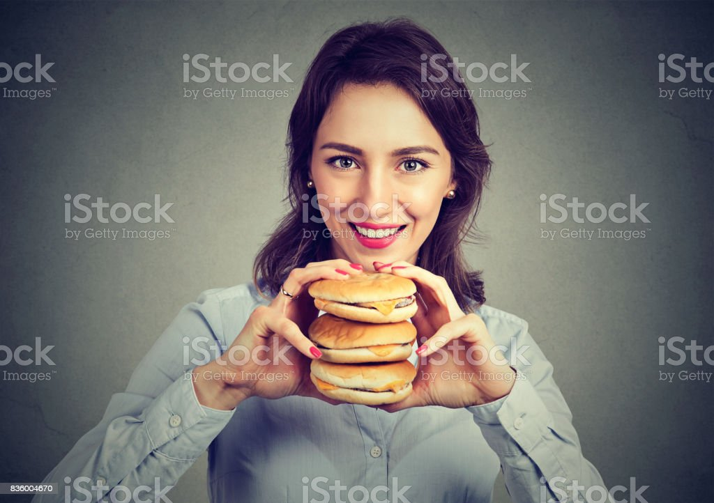 Hungry woman with a tasty triple burger stock photo