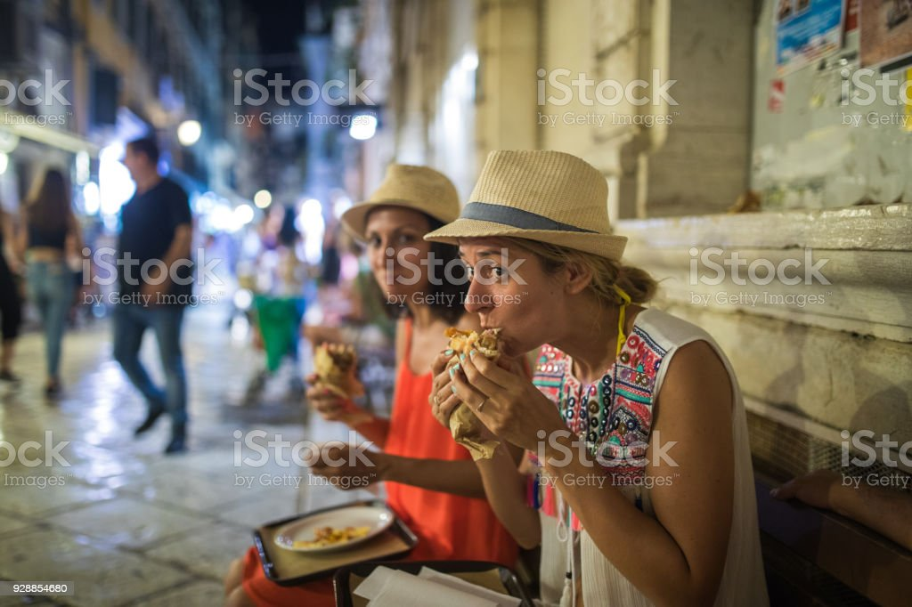 Hungry Young Tourists eating Gyros in Corfu town stock photo