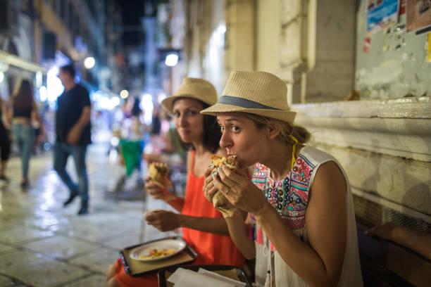 hungrige junge touristen essen gyros in korfu-stadt - streetfood stock-fotos und bilder