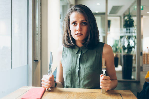 Hungry young woman waiting for her lunch stock photo