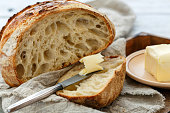 Sliced loaf of artisanal bread and butter knife on linen cloth close-up, selective focus.