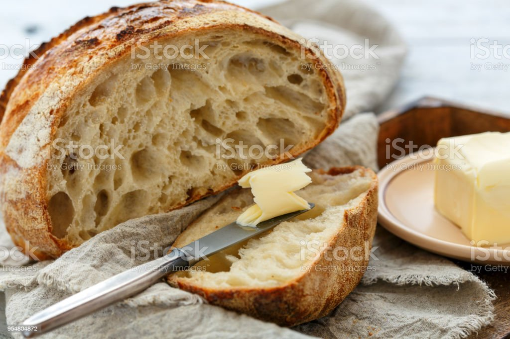 Hunk of French artisanal bread and a knife with butter. stock photo