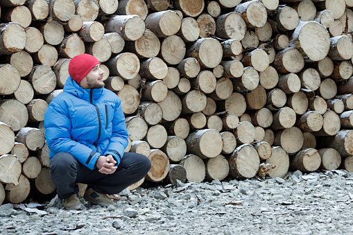Hunkering worker at pile of logged firewood background