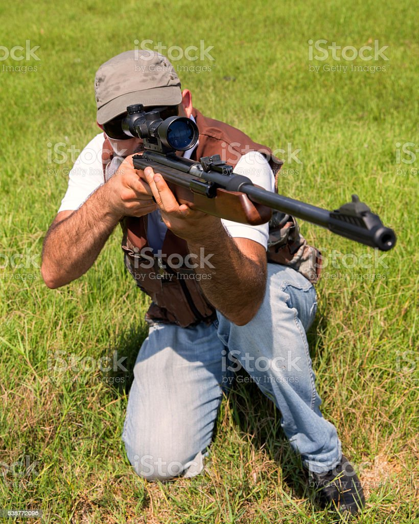 Hunter aiming with rifle stock photo