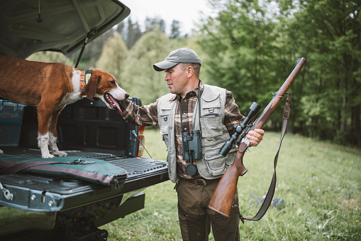 A shot of a hunter with riffle and his dog preparing for a hunt.