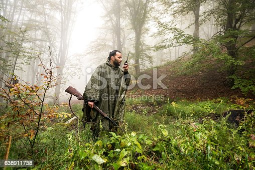 Hunter in the forest holding a rifle and talking to someone over satellite phone.