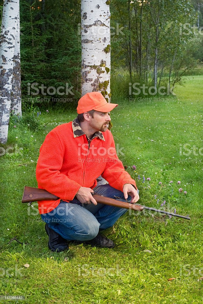 hunter crouching and waiting for prey stock photo