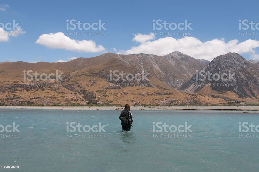 Hunter fording river stock photo