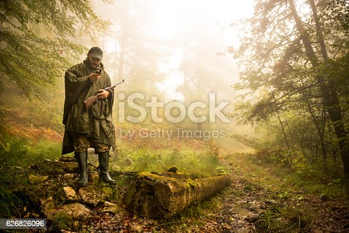 Portrait of hunter with rifle and satellite phone in the forest. There is a fallen tree next to him.