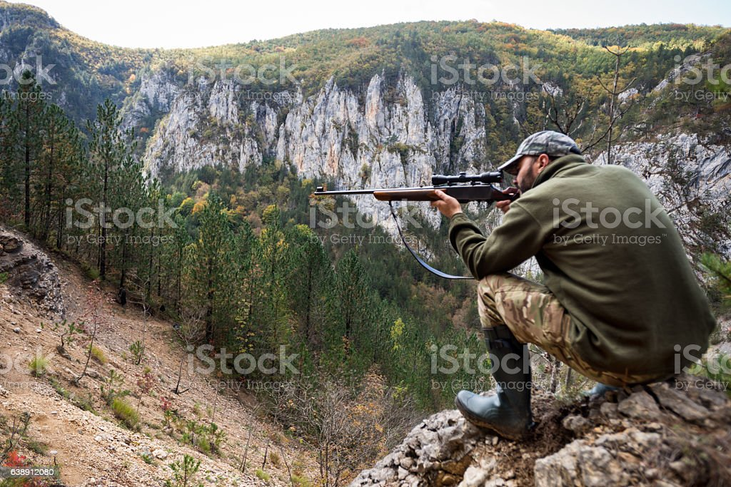 Hunter in the mountains Portrait of hunter with sniper rifle while crouching on top of the hill and aiming at the target. Adult Stock Photo